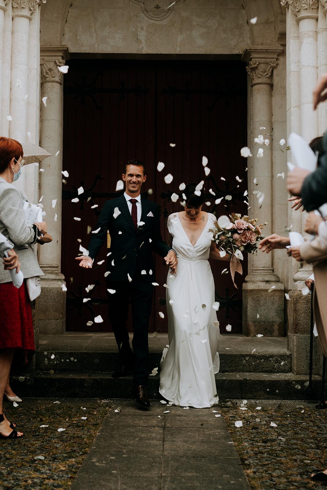 Sortie d'église cérémonie religieuse mariage catholique couple de mariés